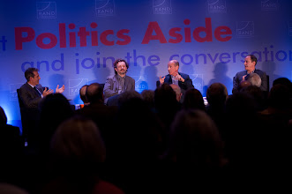 """Photo: Moderator Michael Lynton (far left) and panelist Howard Gordon (third from left) have a spirited exchange during the """"Hollywood and Policy"""" panel discussion Friday, Nov. 16 at the RAND Politics Aside event in Santa Monica as fellow panelists Michael Sheen (second from left) and David Nevins (far right) look on."""