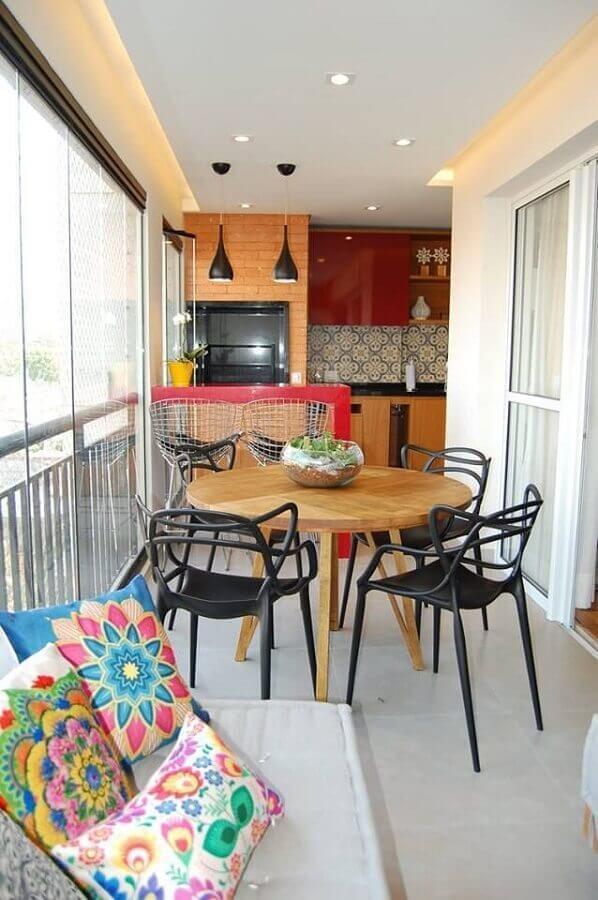 Area gourmet em estilo tradicional e simples com churrasqueira de alvenaria com granito preto, bancada de granito preto, mesa redonda de madeira com cadeiras pretas, piso porcelanato branco.