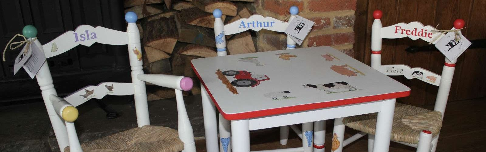 three children's chairs with kids names on them next to a children's table