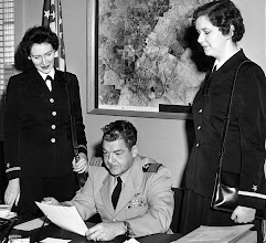Photo: Capt. Duffy exams the orders of Ensigns Mary Duffy and Patricia Harris. Personnel did a double take because the base was commanded by Capt. T.D. Harris before Capt. Duffy took over in July 1958