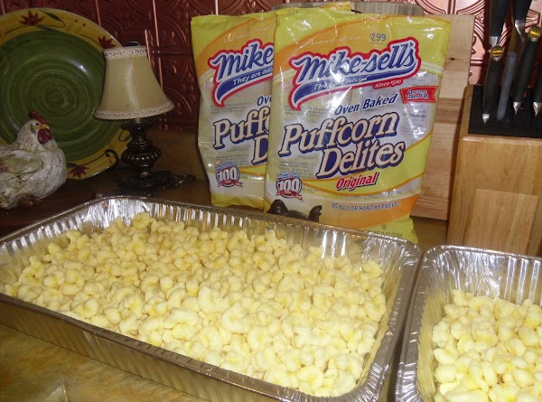 In a large deep aluminum roasting pan pour in:bag of puffed corn1 c. nuts...