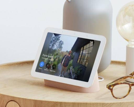 Un NestHub (2ᵉgénération) est posé sur une table en bois à l'intérieur d'un domicile. Sur l'écran, un livreur est devant la porte d'entrée et tient un paquet.