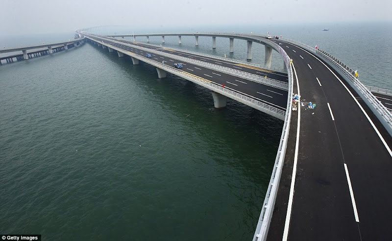 Photo: Lengthy : The bridge  stretches into the distance further than the eye  can see and right, the first few cars roll out  across the surface.