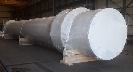 Emballage d'un cylindre en acier dans une pellicule rétractable sur des supports en bois.