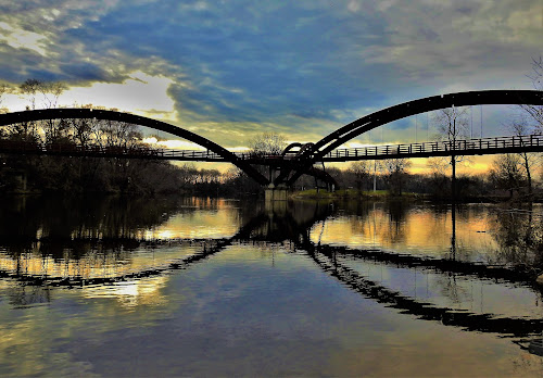 Bridge over Calm Waters by Kathy Woods Booth - Buildings & Architecture Bridges & Suspended Structures ( reflections, riverside, bridge, quiet, mirrored reflections, suspended )