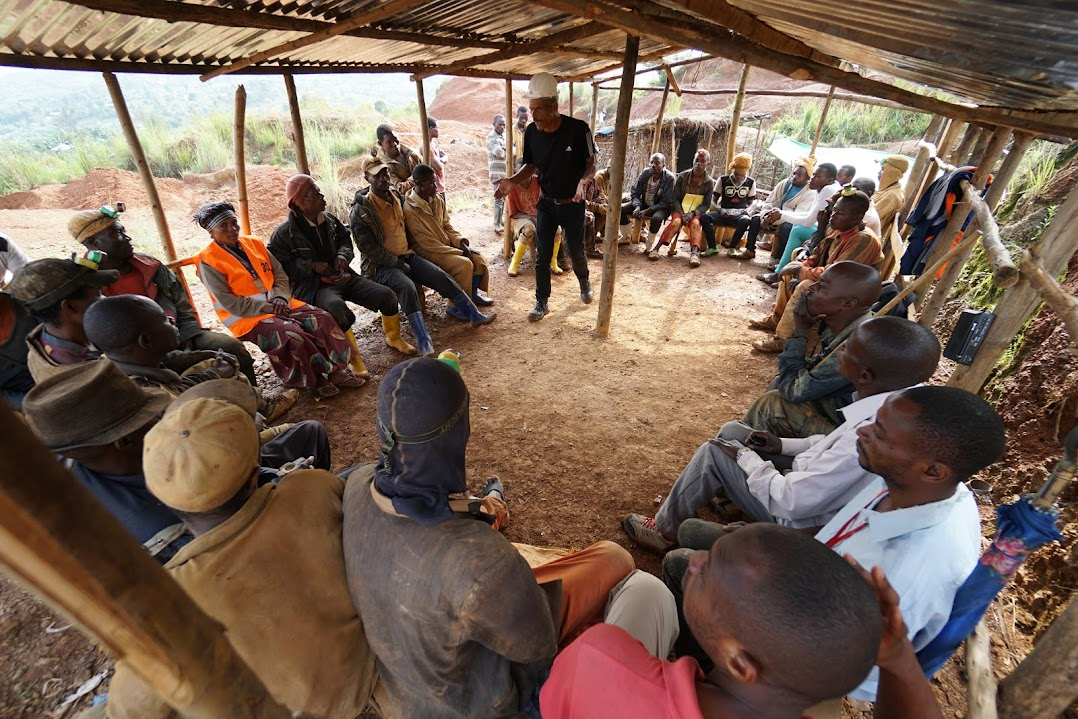 A person leads a morning discussion with fellow miners in the Democratic Republic of Congo.