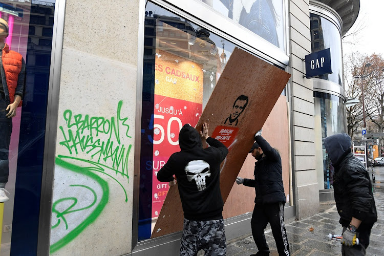 Workmen place a panel over a smashed window at a Gap clothing store a day after 'yellow vest' clashes in Paris, France, December 9 2018. Picture: REUTERS/PIROSCHKA VAN D WOUW