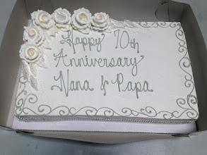 Photo: Platinum Anniversary sheet cake featuring platinum gray writing, silver diamond trim, and white whipped cream frosting roses.