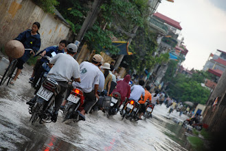 Photo: A Hanoi street (which is under construction) after a shower. In summer, it rains so fast and so heavily that lots of streets are flooded immediately afterward. If you are caught by the rain, riding a bike, it's often not worth it to stop to put on a poncho, by the time you are done putting it on, you are possibly already soaked (and  the rain might have stopped). I like it though, it's cool (literally too).