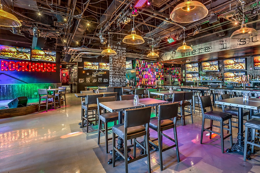 The brightly colored entrance and bar of Rockhouse Las Vegas, serving cheap food and drinks with walls covered in TVs and neon lights