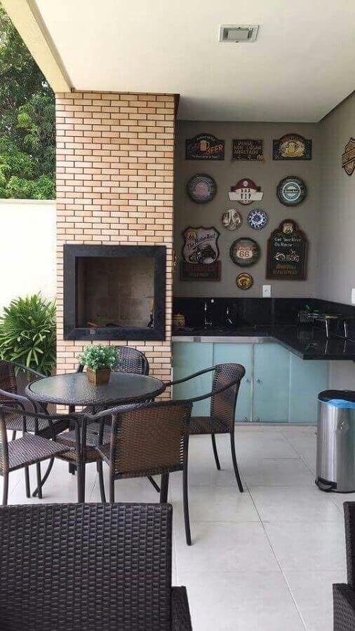 Área externa em estilo moderno com churrasqueira revestida de tijolinhos, armário azul com bancada de mármore preta, quadros decorativo, mesa redonda preta com cadeiras e piso de cerâmica clara.