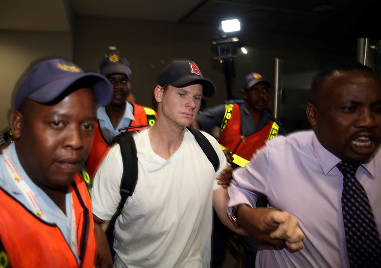 Axed Australian cricket captain Steve Smith is escorted by Police officers as he leaves the OR Tambo International Airport in Johannesburg, March 28 2018. Picture: REUTERS/ SIPHIWE SIBEKO
