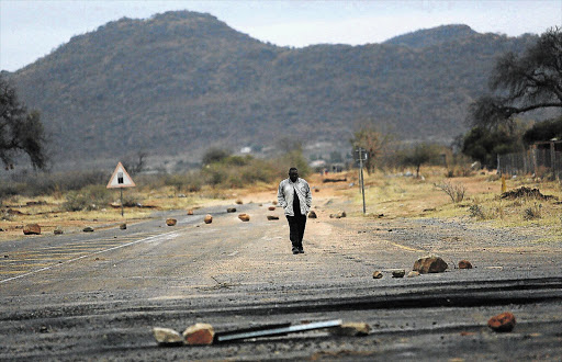 BURNING FUSE: A man walks on a road strewn with rocks leading to Mokopane in Limpopo after a protest by frustrated villagers