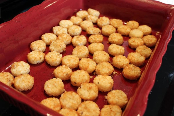 Tater tots lining a red baking dish.