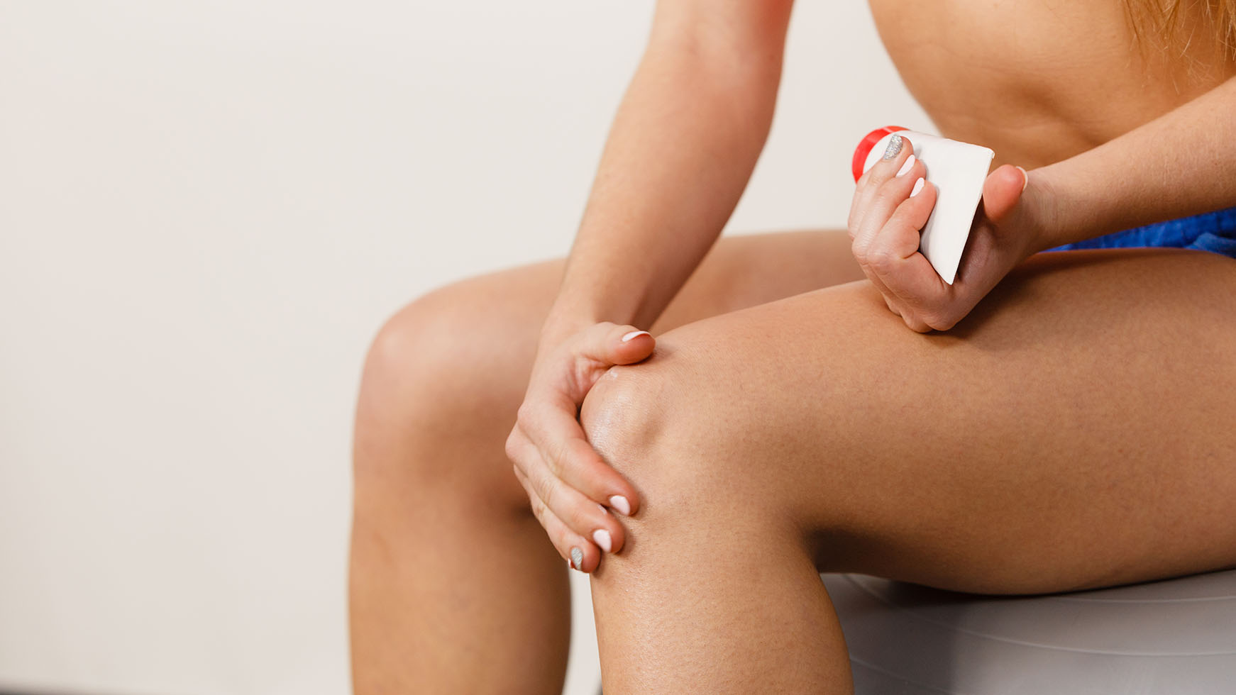 Woman rubbing cream on her painful knee