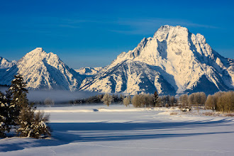 Photo: Oxbow Bend in Grand Teton National Park is an extremely popular spot for photographers. That's not surprising because it really is beautiful, plus it is very accessible - the road runs right along side it and there is plenty of parking.  If you search for images of this location though, you'll hardly see any winter scenes. This is presumably because the road is closed to normal vehicles during the winter, with the only access being on foot, via snowcoach, or snowmobile.  I took this photo when we passed by a couple of weeks ago on snowmobiles while en-route to Old Faithful. Sadly we weren't quite early enough to catch the morning sun on Mt Moran (the peak on the right), but there was still a little mist around at least.  #MountainMonday by +Michael Russell