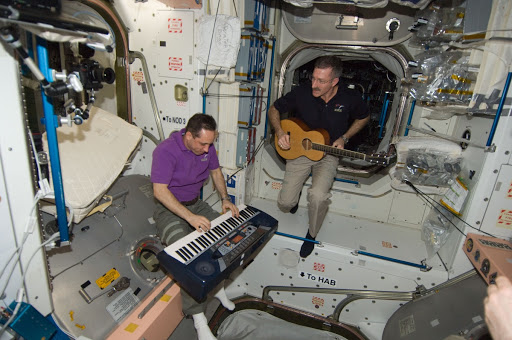 Burbank and Shkaplerov playing musical instruments