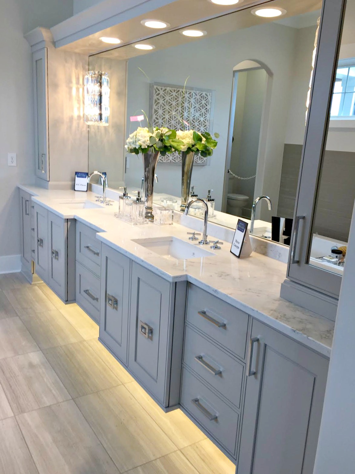 modern vanity with grey cabinets, chrome hardware, double sinks and LED under cabinet lighting