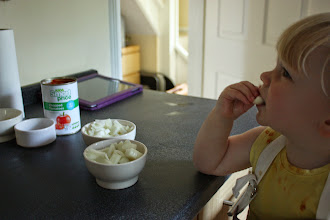 Photo: While the puddings were cooking, Holly helped me make the meat sauce for the pasticcio.  I always encourage the girls to try the ingredients we are using.  Holly was keen to try the raw onion (she has always had a thing about stealing onions from people's kitchens) but she wasn't very impressed with the taste!
