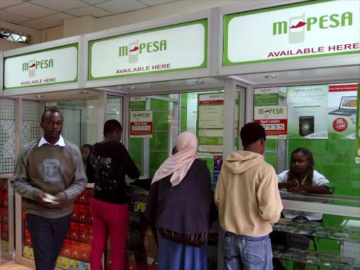 Customers queue outside an M-Pesa shop in Nairobi