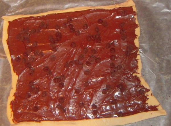 Spread the Nutella evenly over the puff pastry, then sprinkle the nuts over the...