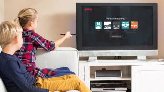 un niño y una niña sentados mirando la pantalla de la televisión