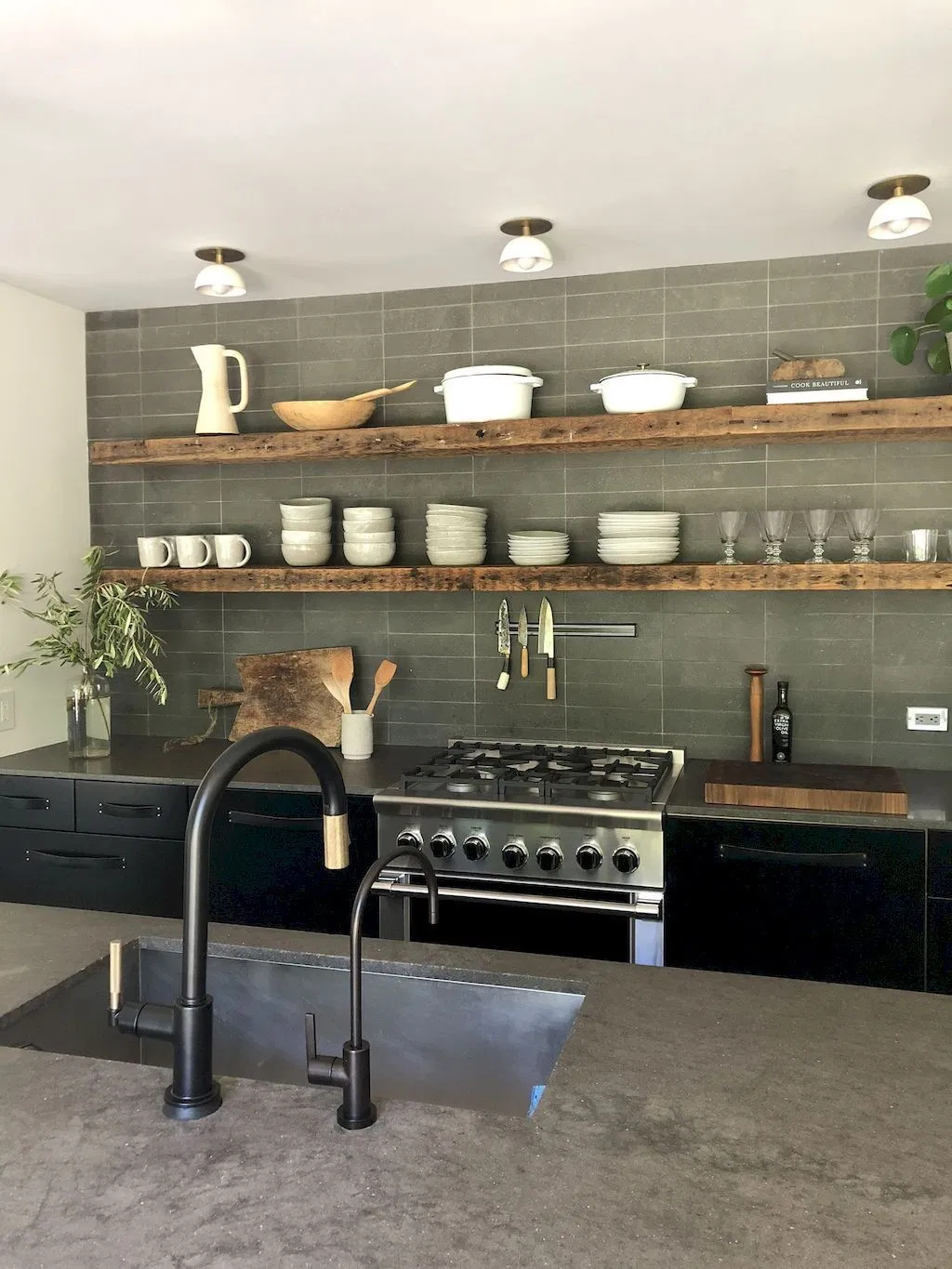darker neutrals in a minimalilst kitchen with cement countertops, matte black sink faucet and black cabinets