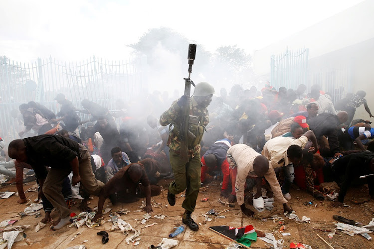 Divided: Panic ensues after Kenyan police fire tear gas at a crowd trying to force their way into a stadium to attend the inauguration of President Uhuru Kenyatta at Kasarani Stadium in Nairobi on Tuesday.  Picture REUTERS