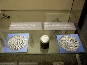 """Photo: Silberner Denar Herzog Heinrichs II. Auf der Vorderseite ist ein Kreuz zu sehen, in drei Winkeln jeweils eine Kugel. Darüber ist die (verbalhornte) Umschrift zu lesen: 'HEIMRICVS DVX'. Auf der Rückseite (rechtes Bild) ist eine """"Letternkirche"""" mit zwei Stufen zu erkennen, darin der Münzmeister 'RAT', darüber 'REGHINA CIVITAS', also Regensburg. Inventar-Nummer im LMO: 2340 L., Dm. 22,5 mm.  Der Denar stammt aus der herzoglichen Münze von  Regensburg. Wahrscheinlich wurde er unter dem Herzog Heinrich II. ('dem Zänker') geprägt (948-955/985-995). Er stammt also noch nicht aus der Zeit seines Sohnes, des Herzogs Heinrich IV, der später als König bzw. Kaiser Heinrich II. regierte (1002-1024). [http://www.landschaftsmuseum.de/Seiten/Aktuell/Denar_Heinrich.htm]"""