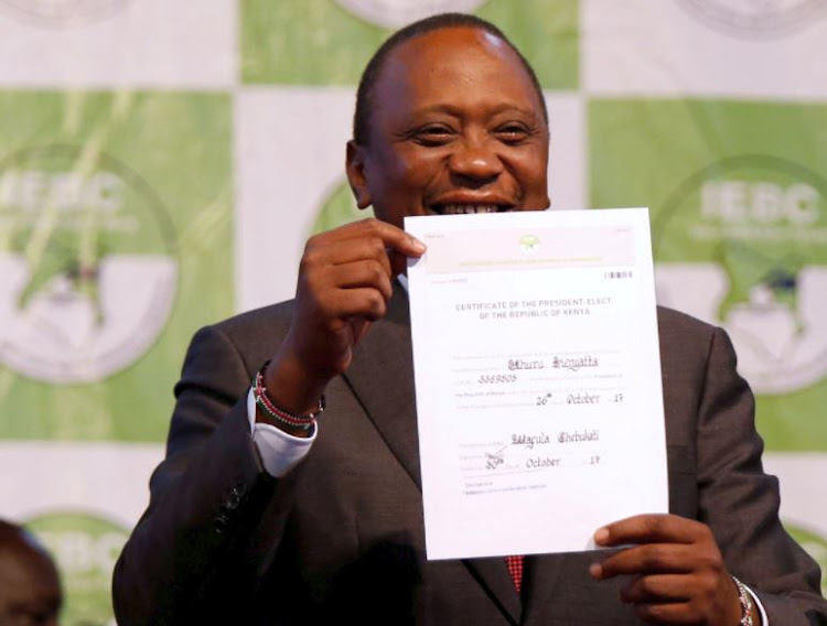 Incumbent President Uhuru Kenyatta holds the certificate of President-Elect of the Republic of Kenya after he was announced winner of the repeat presidential election at the IEBC National Tallying centre at the Bomas of Kenya, in Nairobi October 30, 2017.