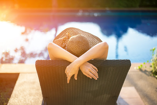 Woman lounging by the refreshing swimming pool