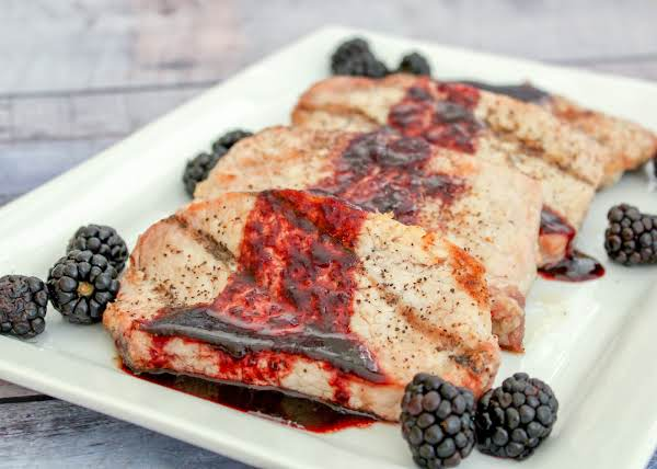 Blackberry Balsamic Reduction Sauce Drizzled Over Grilled Pork Chops.