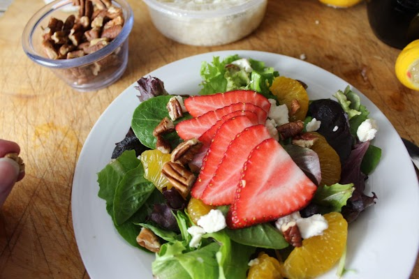 Divide the oranges, strawberries, feta cheese and chopped pecans onto each plate for a...