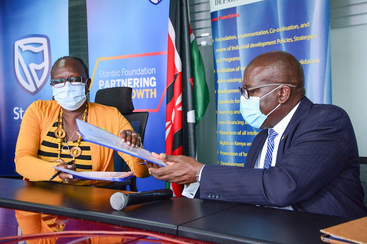 Industrialisation, Trade and Enterprise Development CS Betty Maina exchange notes of the signed MoU with Stanbic Bank Kenya CEO Charles Mudiwa/HANDOUT
