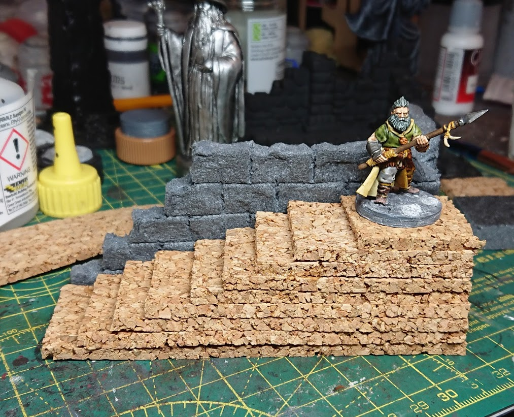 A Frostgrave barbarian on top of the  stairs of an unfinished terrain piece of a ruin.