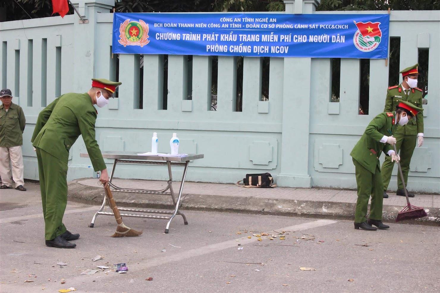 Đoàn viên Phòng Cảnh sát PCCC và Cứu nạn cứu hộ dọn dẹp vệ sinh tại cổng bệnh viện Hữu Nghị Đa khoa Nghệ An trước khi phát khẩu trang.