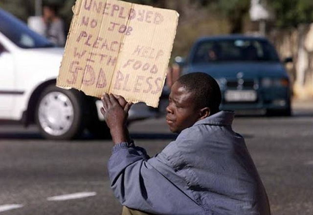 An unemployed young South African pleads for money or food at a street corner