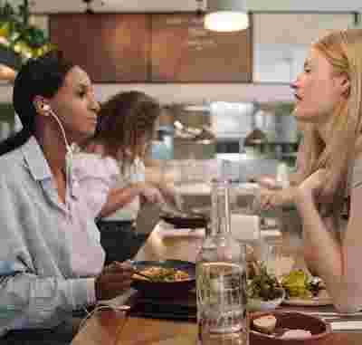 Dos mujeres conversan mientras comen