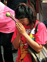 Photo: young woman praying with lotus bud and incense sticks