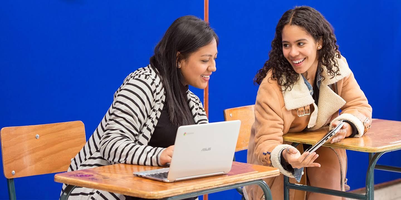 Dos estudiantes en un salón de clases se muestran emocionadas observando el contenido de una tableta.