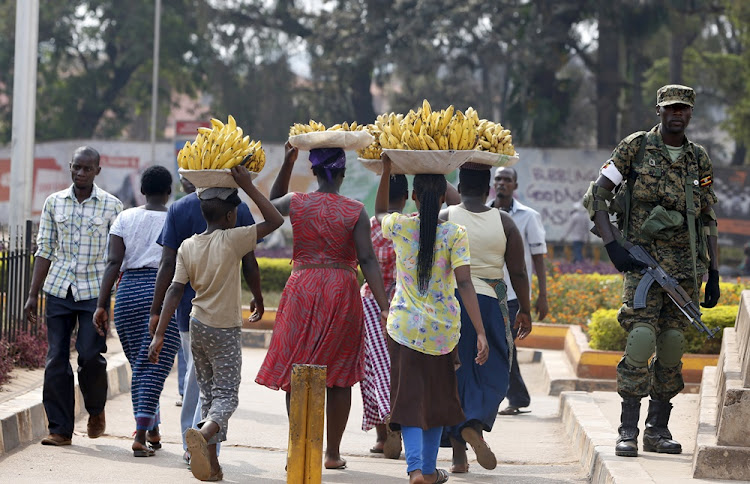 Women carry baskets of banana as they walk past a military personnel patrolling in Kampala, Uganda February 19, 2016.