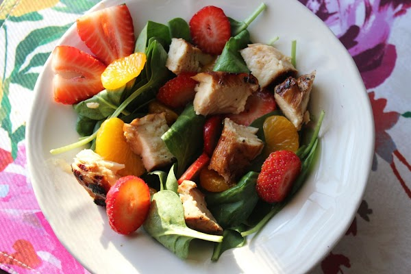 Line 4 individual salad plates with spinach leaves. Arrange oranges, strawberries, and chicken breast...