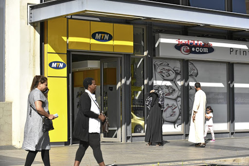 Increasing challenges: People walk past an MTN Store in Rosebank. The group is facing a number of headwinds in its key markets, SA and Nigeria. Picture: FREDDY MAVUNDA