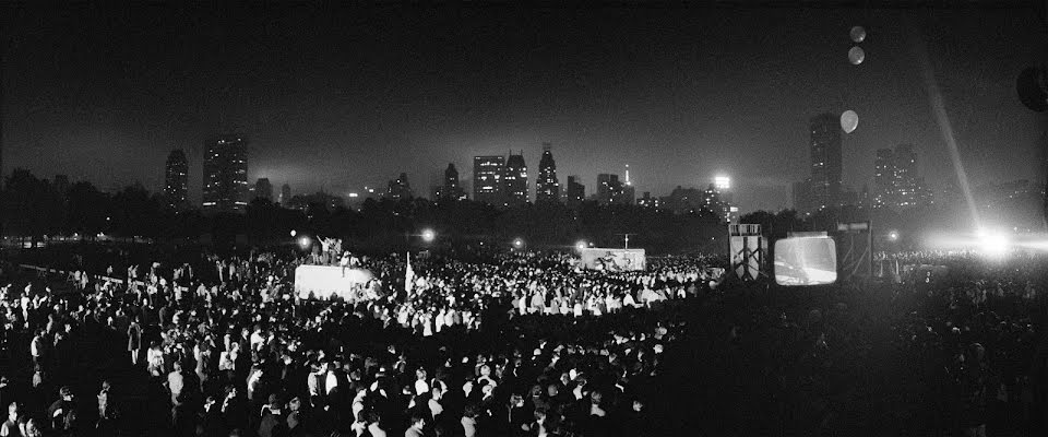 A crowd gathers in the Sheep Meadow of Central Park at night to watch the Apollo 11 Moon Landing