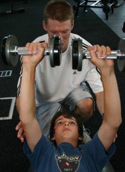 Coach spotting a young teenager lifting weights