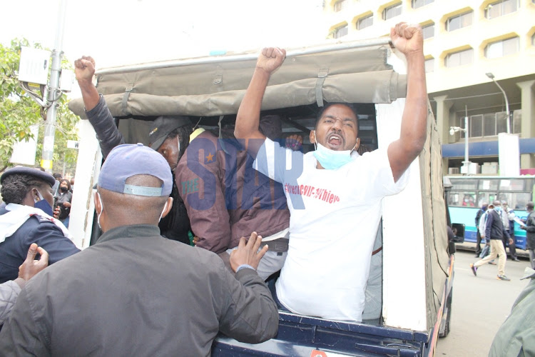 An activist taking part in #ArrestCovid-19Thieves demo is arrested at Nairobi CBD on August 21, 2020/ANDREW KASUKU