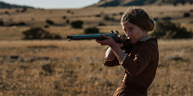 Caitlin Gerard as Lizzie Macklin in The Wind (2018). Lizzie, a young blonde women in a brown dress of the 1800s frontier style, stands alone on the prairie, holding a double barrelled rifle up to her eye.
