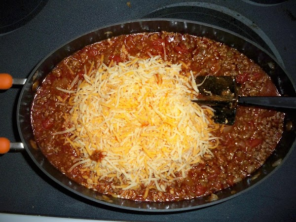 Mix in enchilada sauce, tomato sauce 1/2 shredded cheese and drained tomatoes and chilies.
