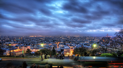 Photo: La Ville de Paris Gets Ready for Night  I was on the hill in the Montmartre part of Paris just after the sun had set. I pointed the camera over the sprawl of the city just as the lights were coming on for the evening. I made it my personal mission to walk down into the city that evening, meander around, and visit at least three pastry shops and eat a silly number of desserts. I tricked myself into thinking that I might be burning a lot of calories by doing so much walking. It's amazing how easily I was able to justify French desserts.  from the blog at www.stuckincustoms.com