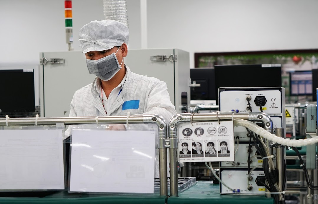 A factory worker at their station wearing a cap and mask.